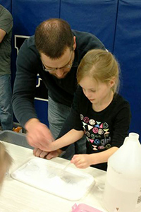 Father and daughter work at one of the science stations