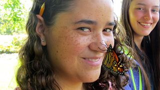 Hamilton District student with Monarch butterfly on her nose