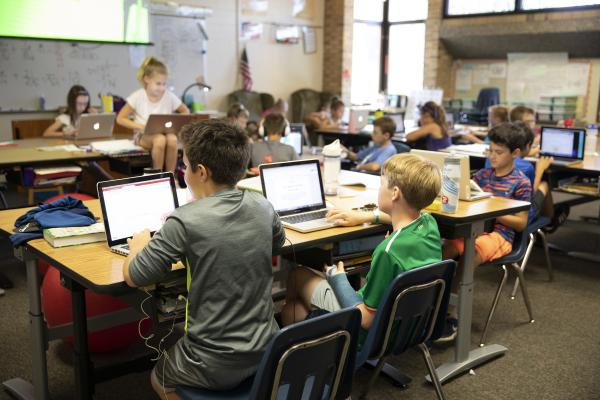 Elementary students using laptops in their classroom